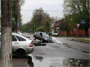 Легковая машина провалилась в дыру на дороге в Брянске